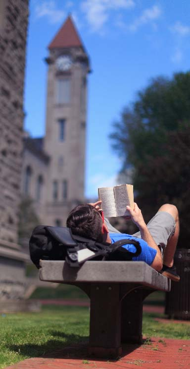 A student reads a book while lying on a bench.