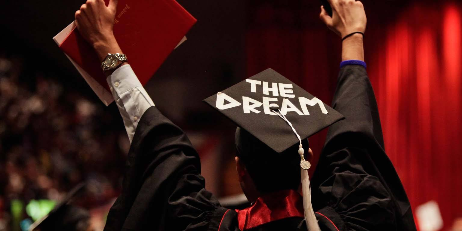 "A back view of graduate with ""THE DREAM"" written on their mortarboard."