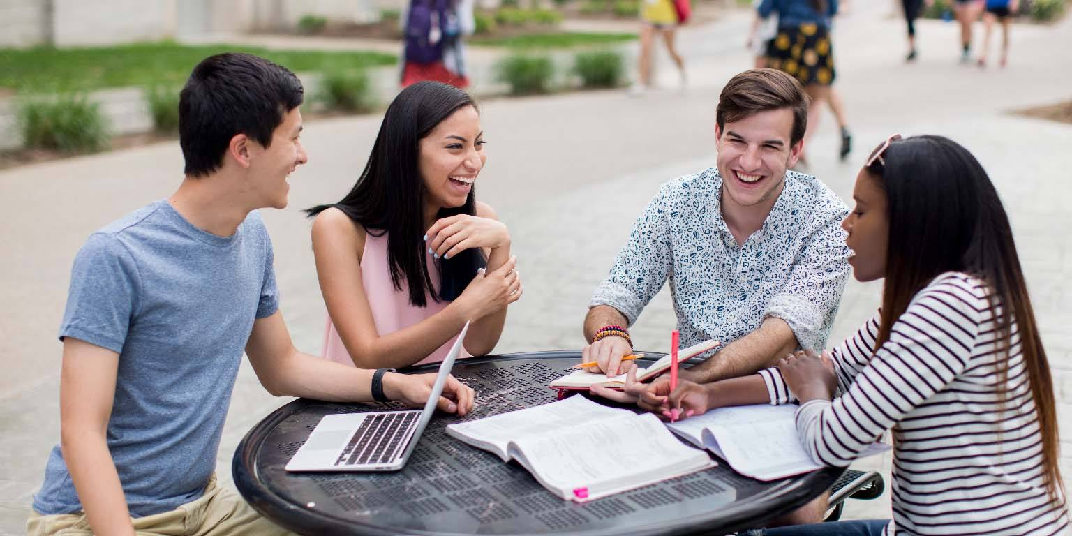 Four students laugh as they sit at a round table covered in books and notes.
