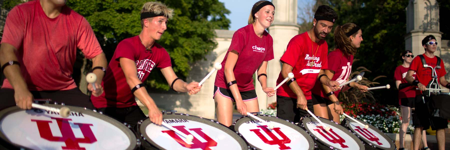 Members of the Marching Hundred play drums on a sunny day.